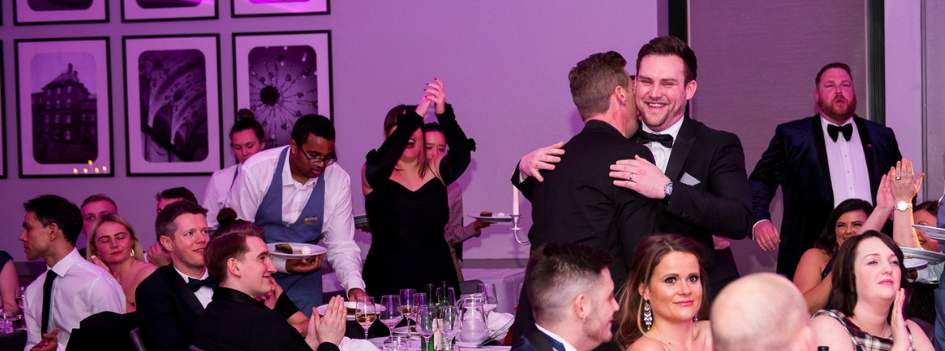 Senior Recruitment Business Partner Sam Blinman hugs a colleague, on his way to the stage during Lorien's 2019 Conference to receive his award 'Best Emerging Tech Recruitment Talent'
